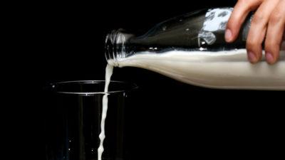 Person pouring milk in glass