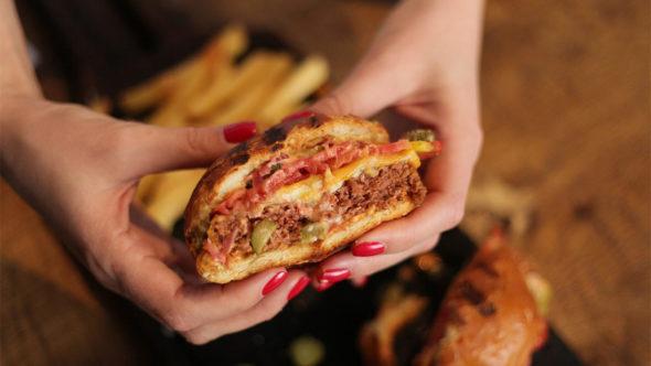 Meat alternatives header of someone holding a vegan burger