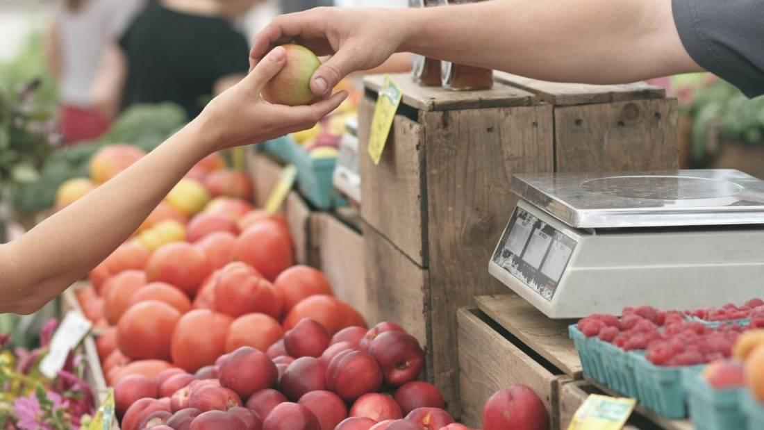 consumer behaviour person handing someone piece of fruit