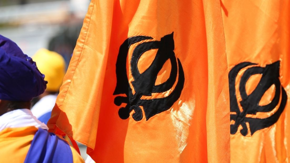 sikh man stands with two orange flags with khanda symbol on them