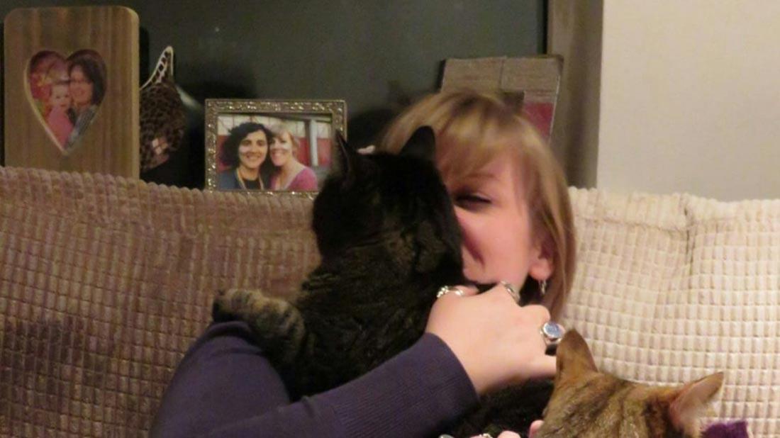 Jess cuddling her cats