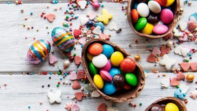 Colourful sweets inside chocolate easter egg on white background