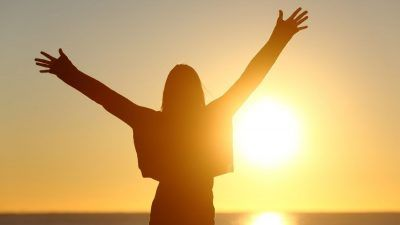 person holding their arms out to the sun